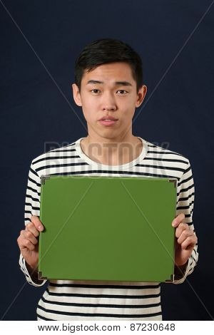 Young Asian man showing green copy space box and looking at camera