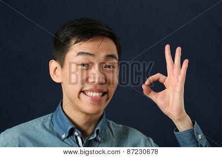 Smiling young Asian man giving okay sign