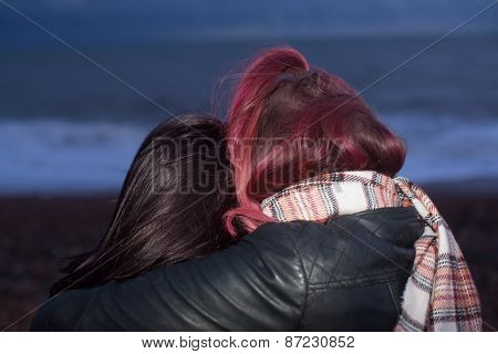 Close Up Of Women Hugging On Beach At Dusk
