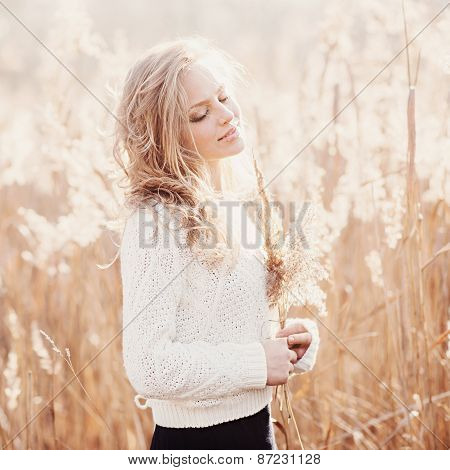 Portrait Of A Beautiful Blonde Girl In A Field In White Pullover, Smiling With Eyes Closed