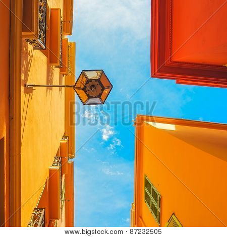 Urban Abstract. Street Lamp, Red Yellow Orange House Facade And Blue Sky Background