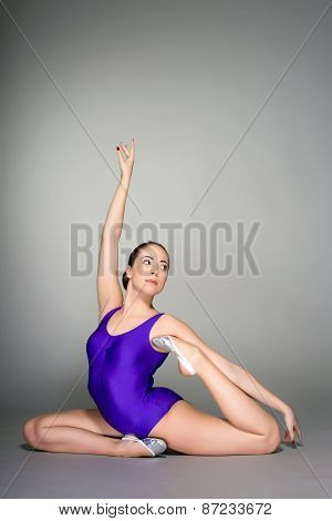 Young Female Contortionist In Purple Leotard On Dark Background