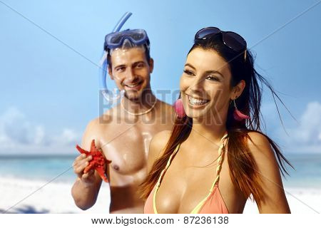 Beautiful young woman smiling happy on the beach, boyfriend holding sea star in hand.