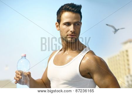 Young athletic man jogging outdoors, holding water bottle.