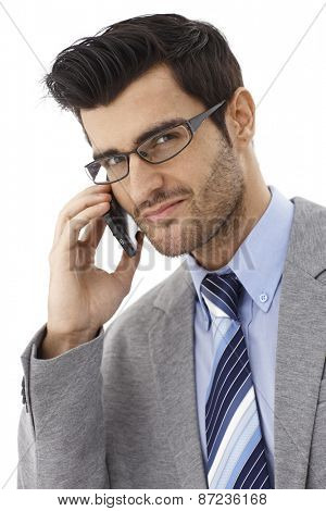 Close-up portrait of handsome businessman chatting on mobilephone, smiling, looking at camera.