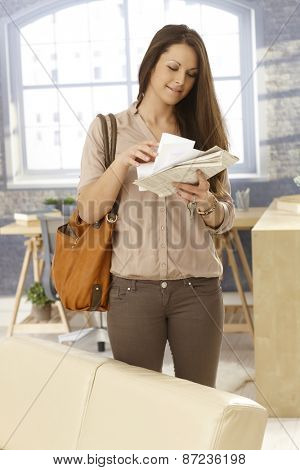 Young woman looking at mail while arriving at home.