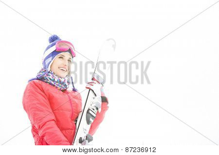 Smiling young woman carrying skis in snow