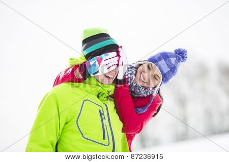 Smiling young woman covering man's eyes in winter