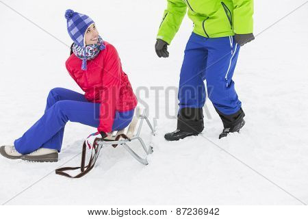 Happy young woman sitting on sled while looking at man in snow