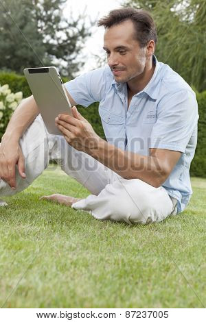 Young man using tablet computer in park