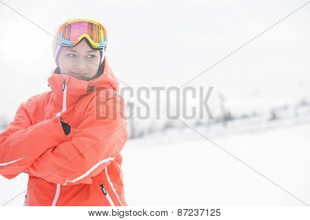 Happy young woman in warm clothing standing arms crossed on snowy field