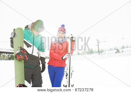 Happy young couple with snowboard and skis in snow
