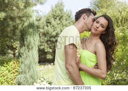 Young man kissing woman in park