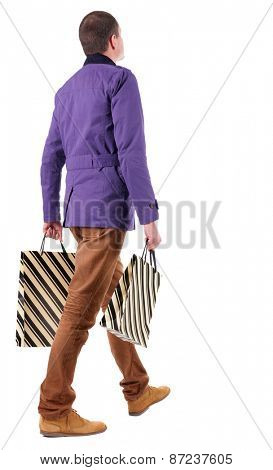 Back view of going  handsome man with shopping bags.  walking young guy is shopping. Rear view people collection.  backside view of person.  Isolated over white background.