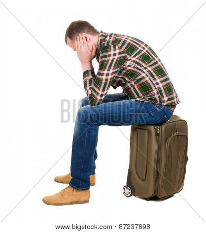 back view of a man sitting on a suitcase. waiting at the station. backside view of person.  Rear view people collection. Isolated over white background.