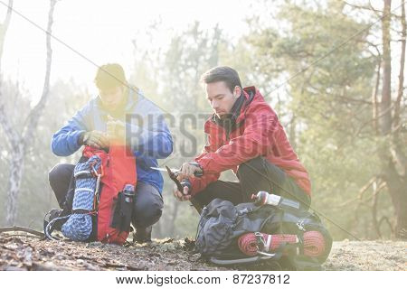 Male backpacker with friend whittling wood in forest