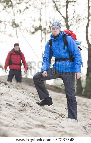 Male hiker at forest with friend in background