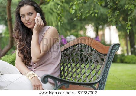 Beautiful young woman looking away while on call in park