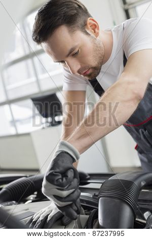 Young maintenance engineer repairing car in automobile store