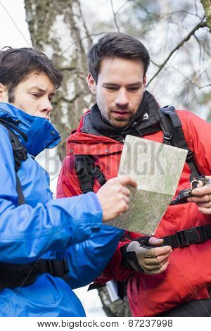 Male backpackers reading map together in forest