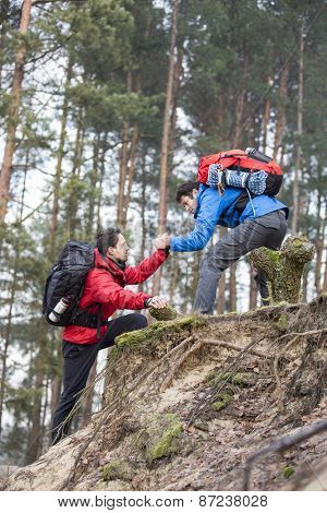 Young backpacker assisting friend while hiking in forest