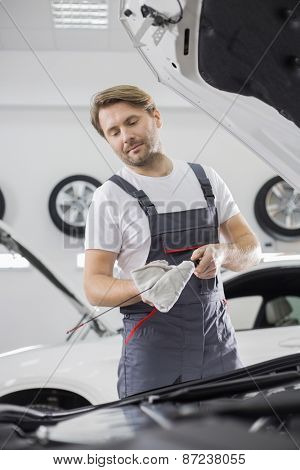 Male mechanic checking oil in car workshop