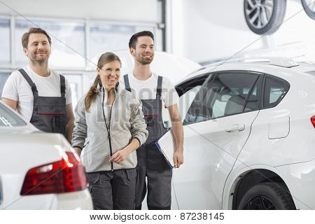 Happy maintenance engineers looking away in automobile repair shop