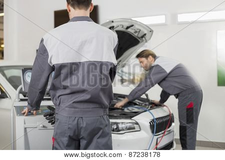 Male maintenance engineers examining car in workshop