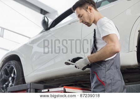 Side view of repairman holding tool while standing by car in workshop