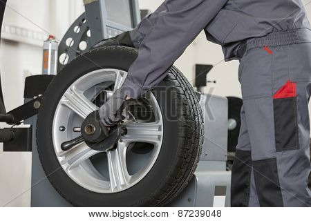 Midsection of male mechanic repairing car's wheel in repair shop