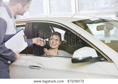 Smiling female customer receiving car key from mechanic in workshop