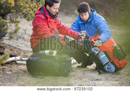 Male backpackers looking at rope in forest