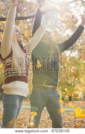 Happy young couple with arms raised enjoying falling autumn leaves in park