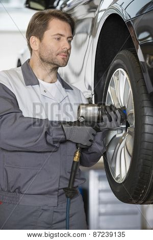 Repairman adjusting car's wheel in workshop