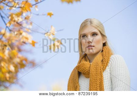 Low angle view of thoughtful young woman against sky