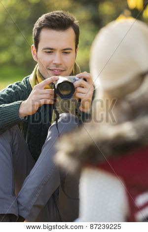 Young man photographing woman in park