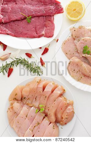 some plates with different raw meat such as turkey fillets, and chicken and beef meat, on a white table