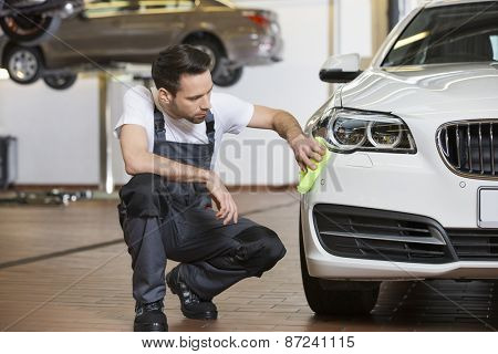 Full length of maintenance engineer cleaning car in workshop