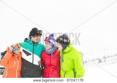 Cheerful young friends standing arm around in snow
