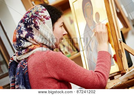 Religious icon painter woman paints a new icon with brush at workshop
