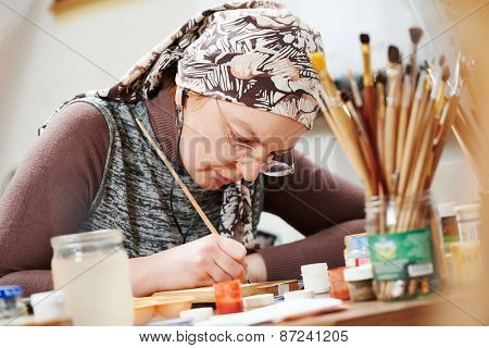 iconography. painter woman paints a new icon with brush at workshop
