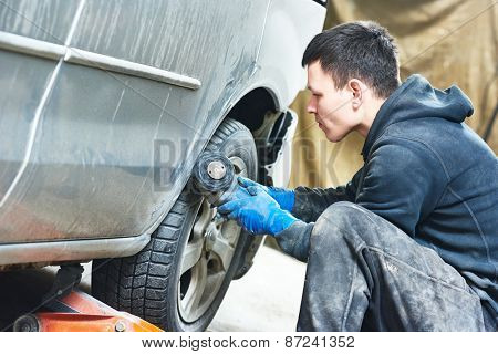 auto mechanic worker sanding polishing bumper car at automobile repair and renew service station shop by polishing ggrinding machine