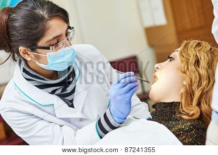 female dentist doctor during tooth examination and treatment