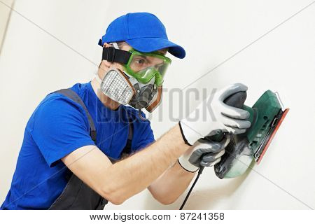 Home improvement plasterer worker in protective mask and glasses working with sander for smoothing wall surface