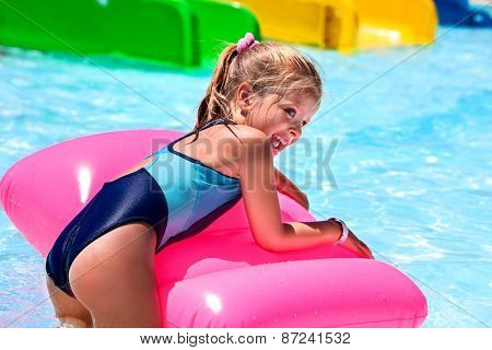 Child on blue water slide at aquapark. Summer holiday.