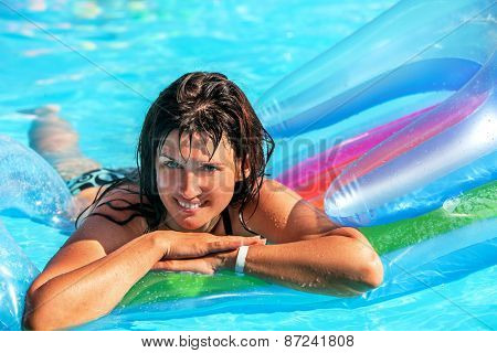 Happy woman  swimming on inflatable beach mattress.Portrait.