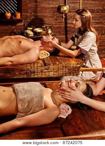 Couple  having oil Ayurveda spa treatment. Wooden table.Facial massage.