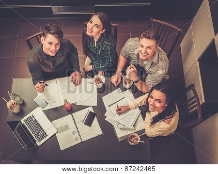 Group of cheerful students preparing for exams