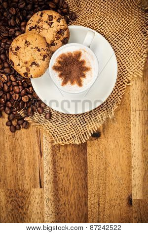 Cup of coffee served in porcelain saucer on wooden table. Shot from aerial view