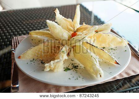 Deep fried eggplant in tempura coating on table